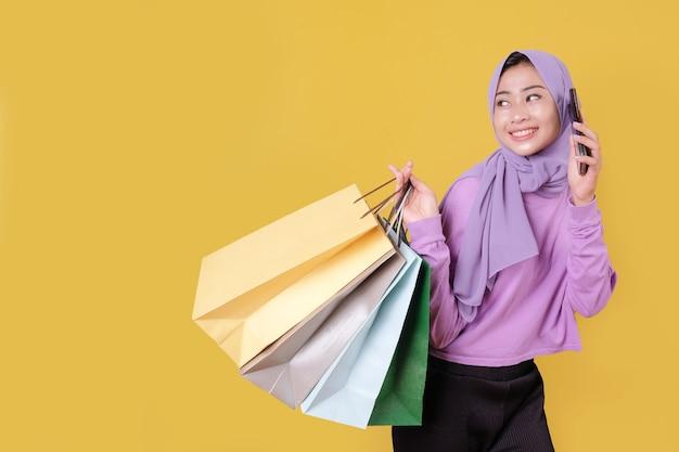 Beautiful asian woman showing shopping bags, wearing purple t shirt, using mobile phone