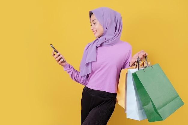 Beautiful asian woman showing shopping bags, wearing purple t shirt