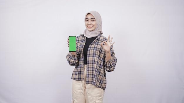Красивая азиатская женщина, показывающая экран смартфона, жестикулирующая хорошо изолирована на белом фоне
