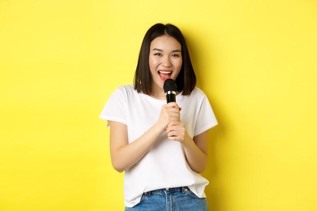 아름 다운 아시아 여자 노래 노래방, 마이크와 함께 수행 하 고 노란색 배경 위에 서 행복 하 고 카메라를보고 웃 고.