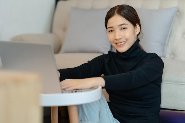 居間に座って所得税を計算する美しいアジアの女性