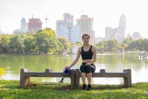 운동에 대 한 준비가 공원에 앉아 아름 다운 아시아 여자