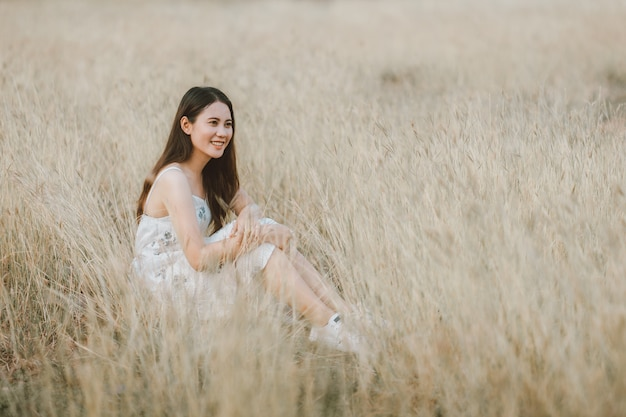 Красивейшая азиатская женщина сидя естественный лужок и имеет чувство свободы