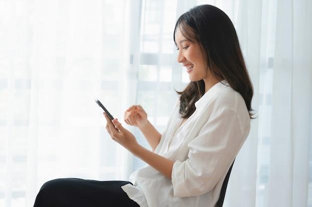 아름다운 아시아 여성이 의자에 앉아 소셜 미디어에 문자 메시지가 있는 스마트폰을 들고 있습니다.