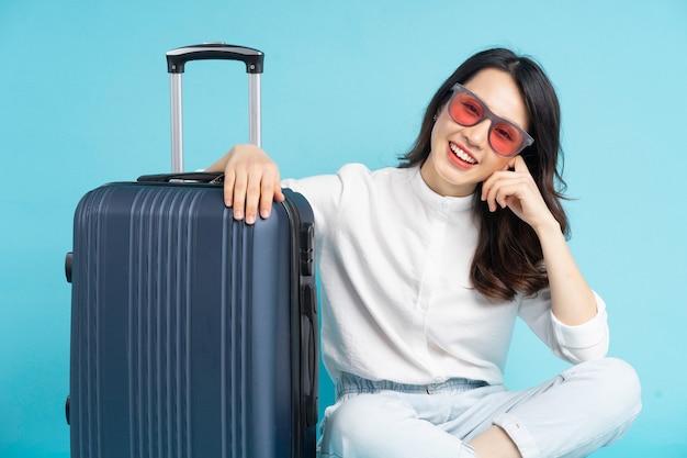 Красивая азиатская женщина сидит, позирует рядом с чемоданом и готовится к путешествию