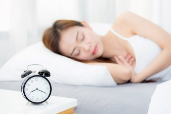 Beautiful asian woman sleeping lying in bed comfortable and happy with alarm clock.