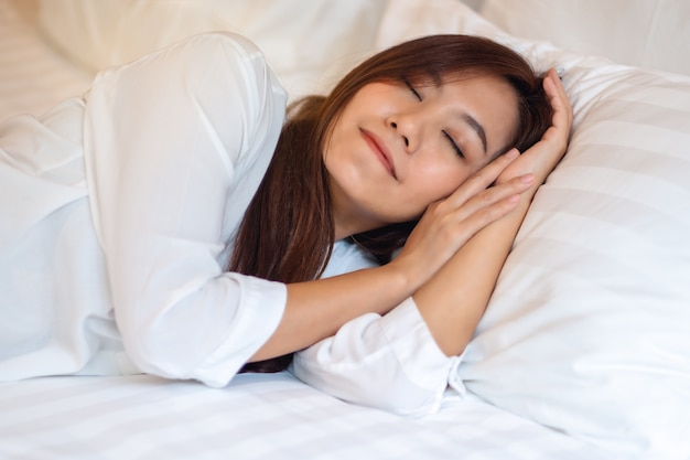 A beautiful asian woman sleeping in a white cozy bed at home