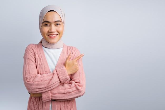 美しいアジアの女性の笑顔と空きスペースを指しています