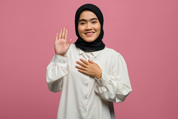 Красивая азиатская женщина улыбается и приветствует в белой рубашке