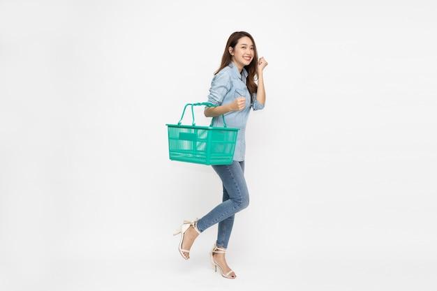 Красивая азиатская женщина улыбается и держит корзину для покупок на белом фоне