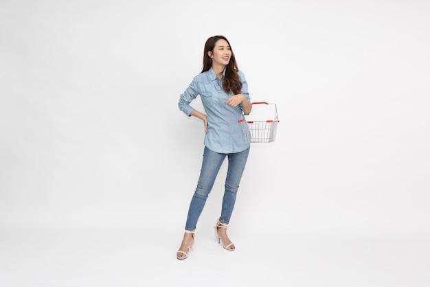 아름 다운 아시아 여자 웃 고 흰색 배경에 고립 된 쇼핑 바구니를 들고