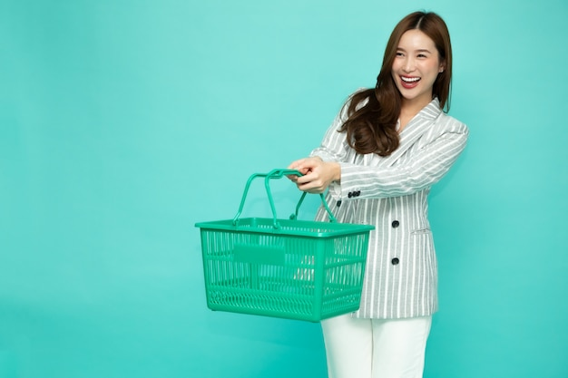 웃 고 쇼핑 바구니를 들고 아름 다운 아시아 여자