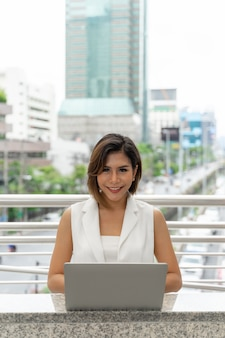 Beautiful asian woman smiling in business woman clothes using laptop computer and smartphone