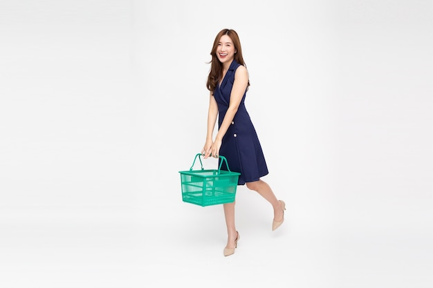 Beautiful asian woman smiling and holding shopping basket in full body isolated on white background