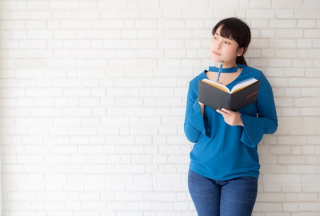 Beautiful asian woman smiling standing thinking and writing notebook
