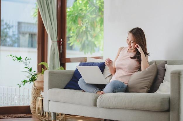 거실에서 노트북을 통해 집에서 일하는 동안 웃고 있는 아름다운 아시아 여성