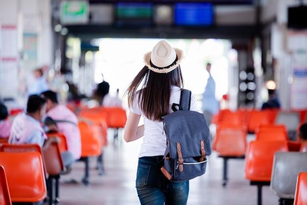 地図とバスステーションでバッグに笑みを浮かべて美しいアジアの女性