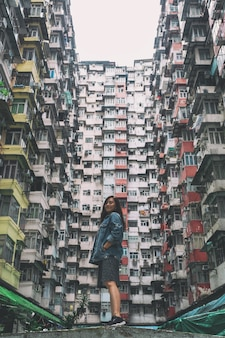 A beautiful asian woman standing among the crowded residential building of the community in quarry bay, hong kong