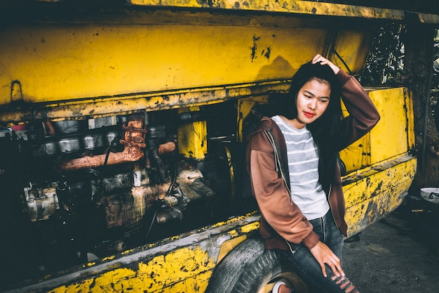 Beautiful asian woman standing beside car engine