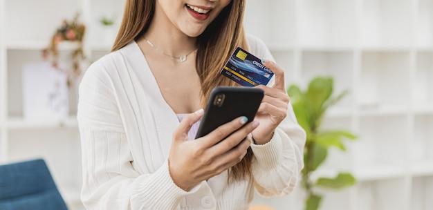 スマートフォンとクレジットカードを持って立っている美しいアジア人女性。彼女はクレジットカード情報を入力して商品やサービスの支払いを行い、オンラインショッピングのコンセプトはクレジットカードで支払い、スマートフォンで使用します。