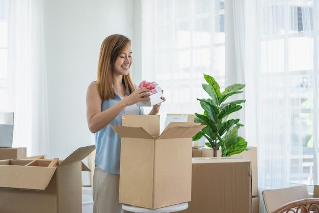 아름다운 아시아 여성이 거실에 있는 새 집으로 이사하는 동안 서서 마분지로 선물 상자를 엽니다