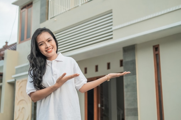 Beautiful asian woman stands with a hand gesture to offer something in front of the new house