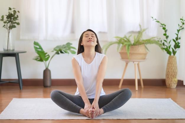 健康的なトレンドライフスタイルのために自宅で運動することによって健康を維持する美しいアジアの女性
