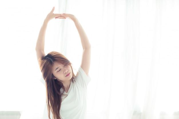 Красивая азиатская женщина растягивается и расслабляется в постели