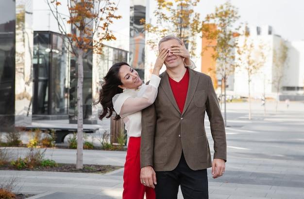 아름다운 아시아 여성이 거리의 세련된 커플에게 눈을 감고 남자 친구를 놀라게 합니다.
