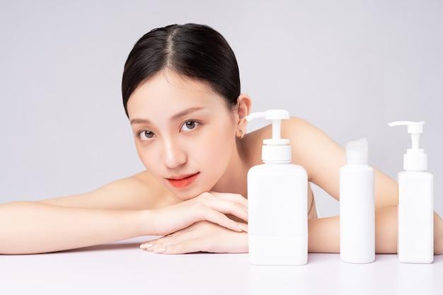 自然な製品で肌をケアする美しいアジアの女性