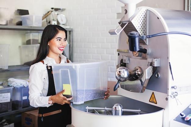 ロースタリーからコーヒーを取る美しいアジアの女性