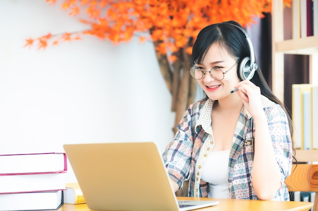 A beautiful asian woman in thailand wearing glasses and a plaid shirt, she is looking at a laptop computer and has headphones on the table. in the concept of learning or teleconferencing via online.