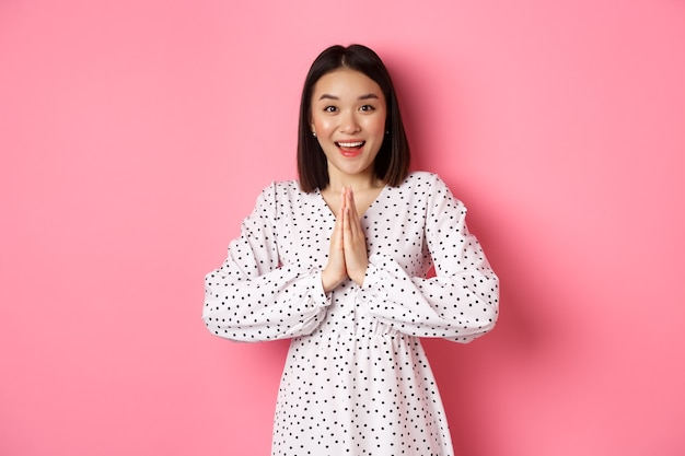 Красивая азиатская женщина благодарит вас, взявшись за руки вместе в знак признательности, улыбаясь счастливой в камеру, благодарно стоя на розовом фоне.