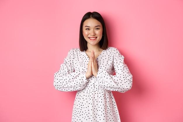 아름 다운 아시아 여자 감사, 감사 제스처에 함께 손을 잡고 카메라에 행복 미소, 핑크 위에 감사 서.