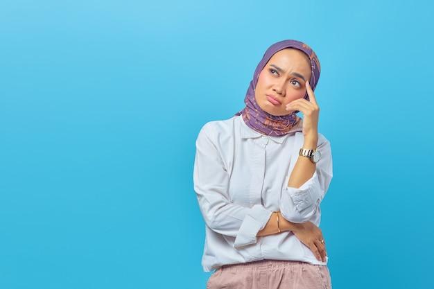 青い背景に分離されたアイデアを考えている美しいアジアの女性