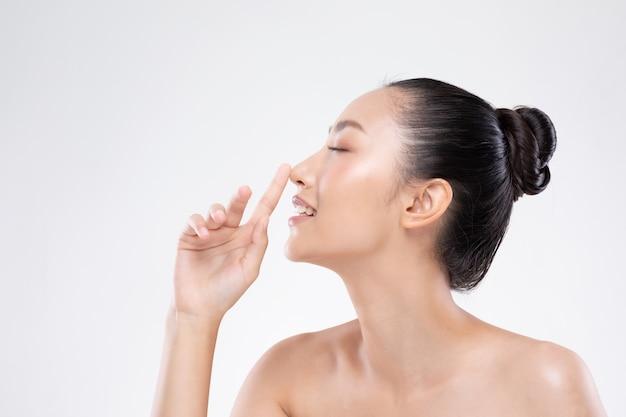 清潔で新鮮な肌と鼻笑顔に触れる美しいアジアの女性幸福と肯定的な感情的な陽気