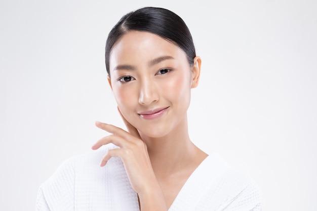 清潔で新鮮な肌と柔らかい頬笑顔に触れる美しいアジアの女性幸福と肯定的な感情的な陽気