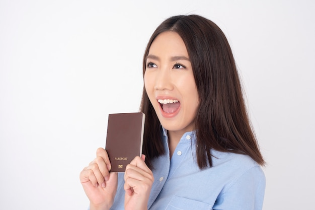 美しいアジアの女性観光客は白い壁にパスポートを保持しています。