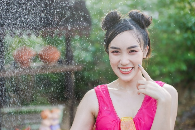Beautiful asian woman in traditional costume of thailand playing water in songkran festiva