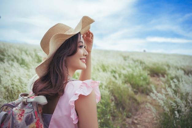 美しいアジアの女性旅行者彼女は牧草地に