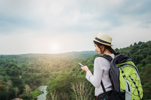 Beautiful asian woman traveler with backpack relaxing in vacation on mountain with using mobile