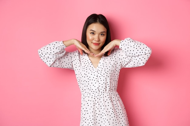 Bella donna asiatica in abito alla moda che fa un viso carino, tenendosi per mano vicino alla mascella e guardando civettuola alla macchina fotografica, in piedi su sfondo rosa