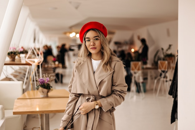 Beautiful asian woman in trendy trench coat and bright beret holds bag and looks into front against cozy room