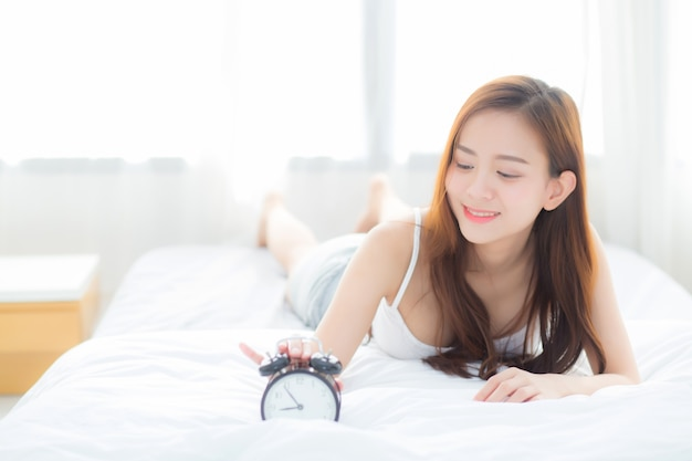 Beautiful asian woman turn off alarm clock in morning.