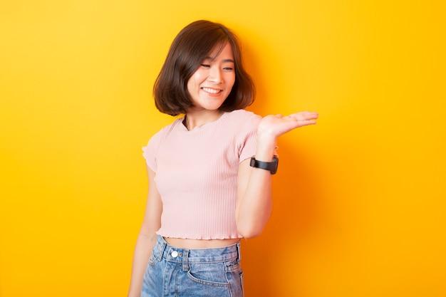 Красивая азиатская студентка университета женщины счастливая на желтой стене