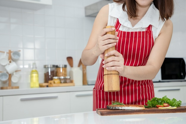 Beautiful asian woman use pepper mill with rosemary in grilled salmon steak on wooden cutting board ideas about healthy cooking and weight loss