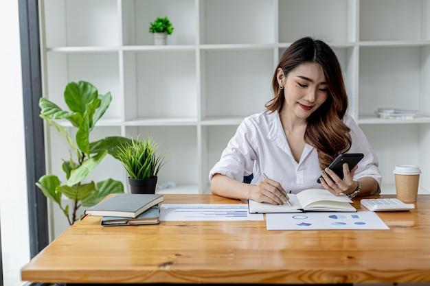 스마트폰을 사용하는 아름다운 아시아 여성, 스마트폰으로 인터넷을 검색하고 노트북에 메모를 하는 사업가, 그녀는 방에서 일하고 있습니다. 인터넷 검색 및 기술 사용의 개념입니다.