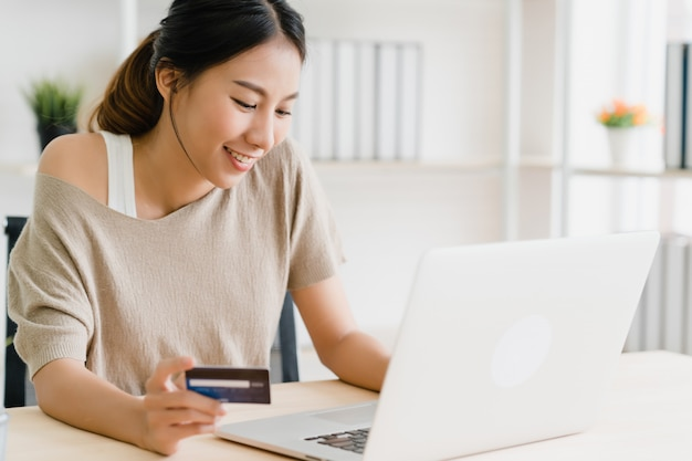 Beautiful asian woman using computer or laptop buying online shopping by credit card