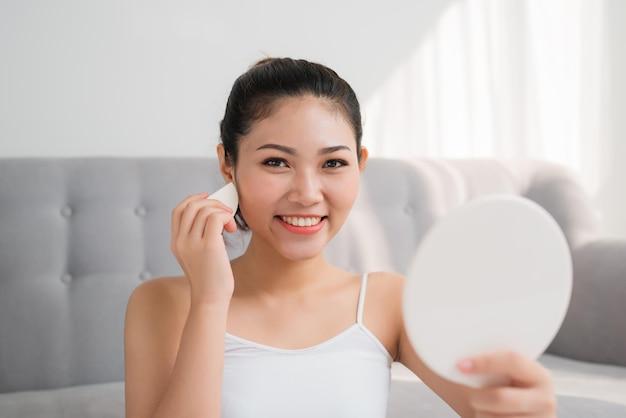 얼굴에 화장용 스펀지를 사용하고 집에서 거울을 보는 아름다운 아시아 여성