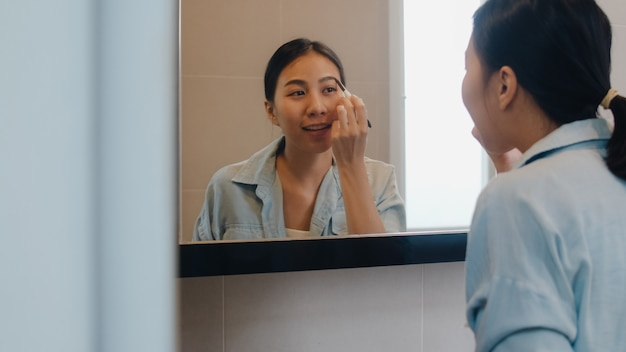 Beautiful asian woman using eyebrow pencil make up in front mirror, happy latin female using beauty cosmetics to improve herself ready to working in bathroom at home. lifestyle women relax at home.